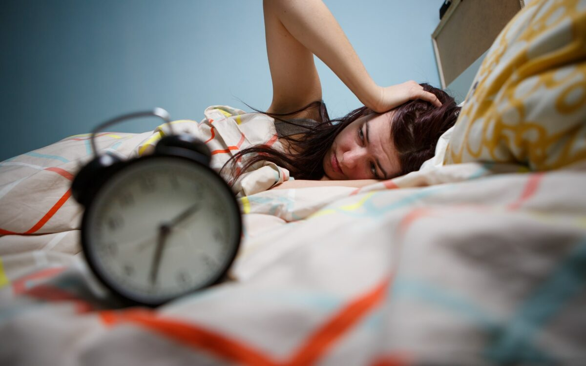 Woman waking up to an early alarm after not enough sleep