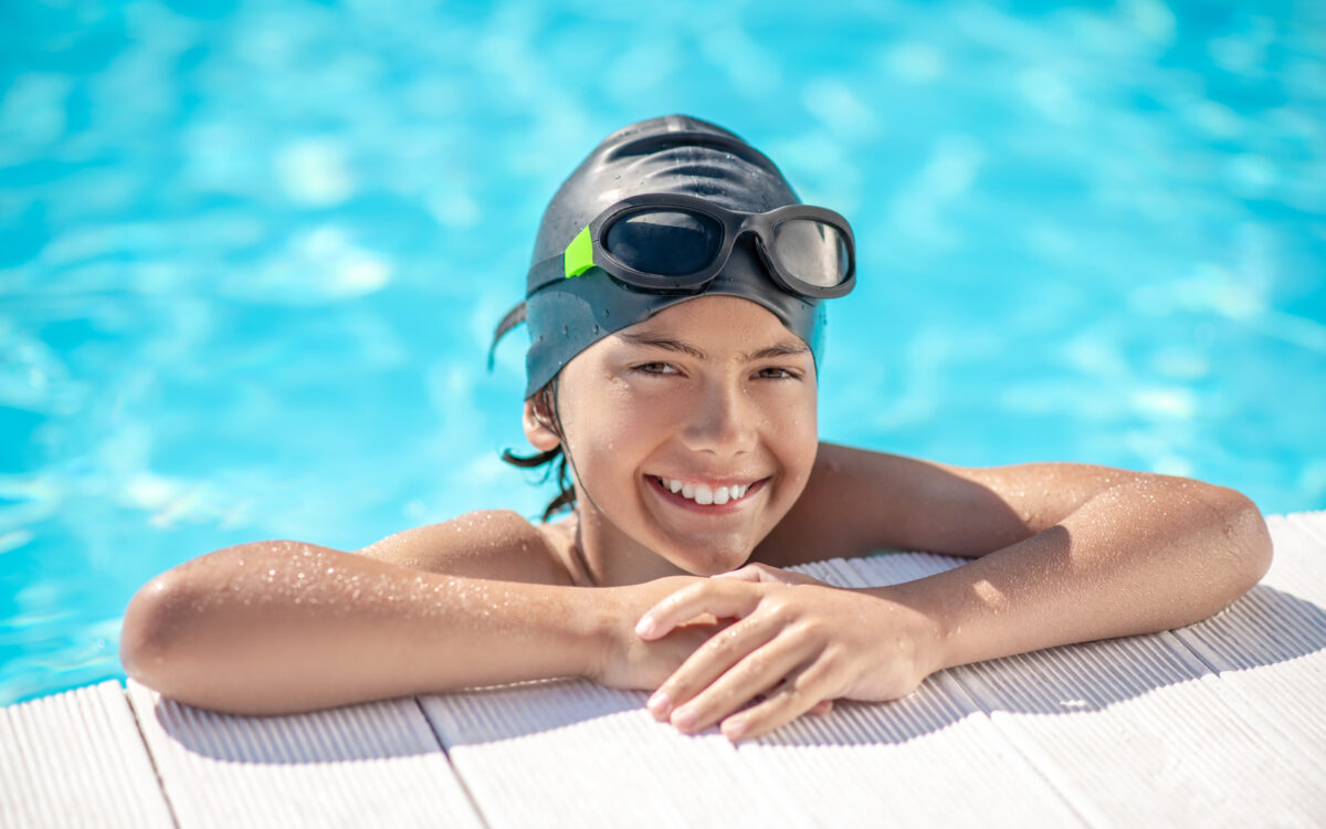 Child smiling in swim gear at the edge of a pool