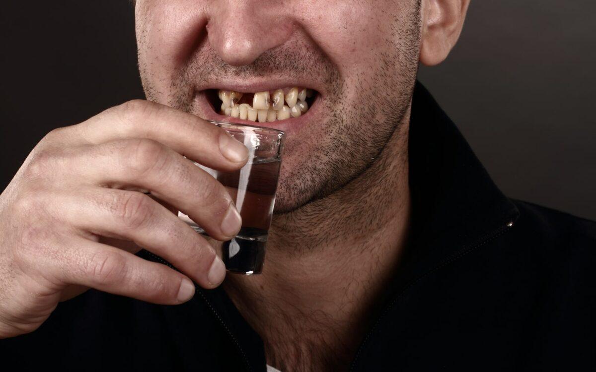 Man with bad teeth drinking alcohol